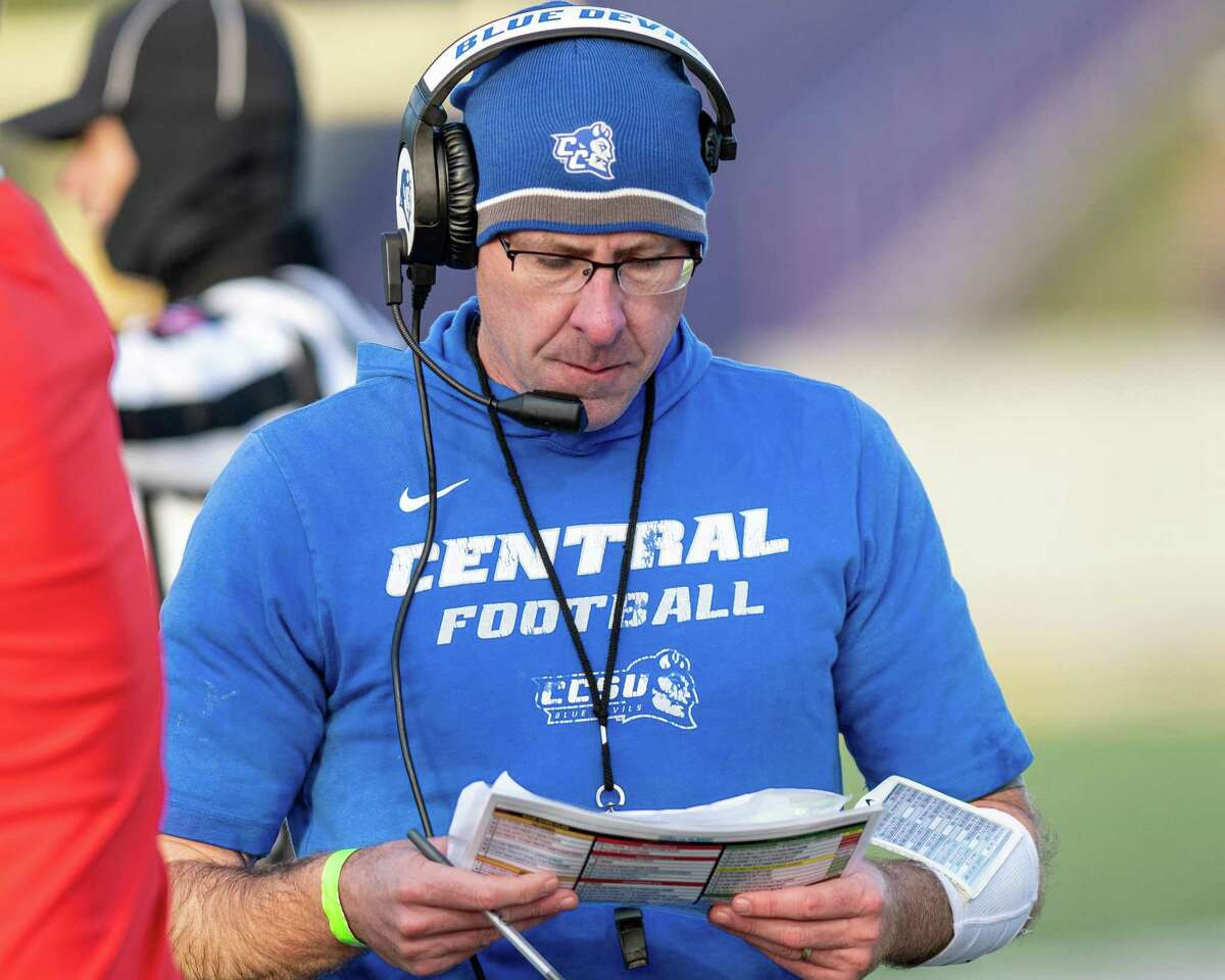 Central Connecticut football coach Ryan McCarthy checks his playbook during the first round of the NCAA playoffs against Albany in 2019.