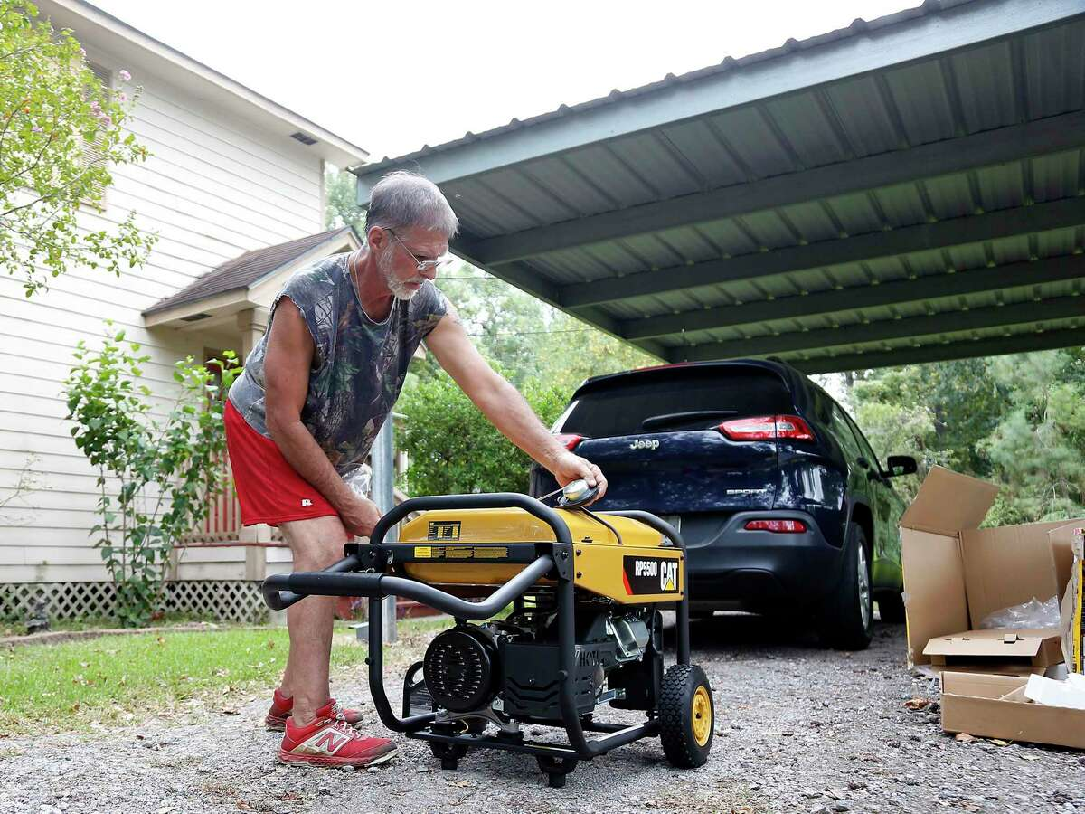 """Randy Philpott assembles a new generator as he prepares to ride out Hurricane Laura in his home in Bridge City on Wednesday, Aug. 26, 2020. Philpott is staying because his mom and aunt, who live close by, have decided not to leave. """"It's heck if you do, it's heck if you don't,"""""""