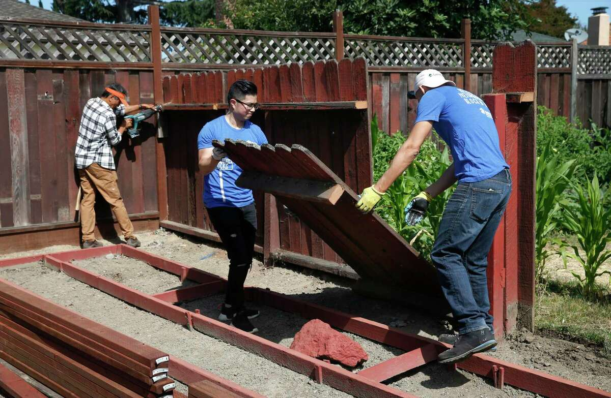 Simon Lo (center) and Pete Holmgren remove an old section of fence before building a new one at a home on Aster Way in East Palo Alto, Calif. on Thursday, July 19, 2018. Dozens of volunteers came together for Habitat for Humanity's Building Blocks program to make critical repairs for long-time homeowners in underserved neighborhoods.