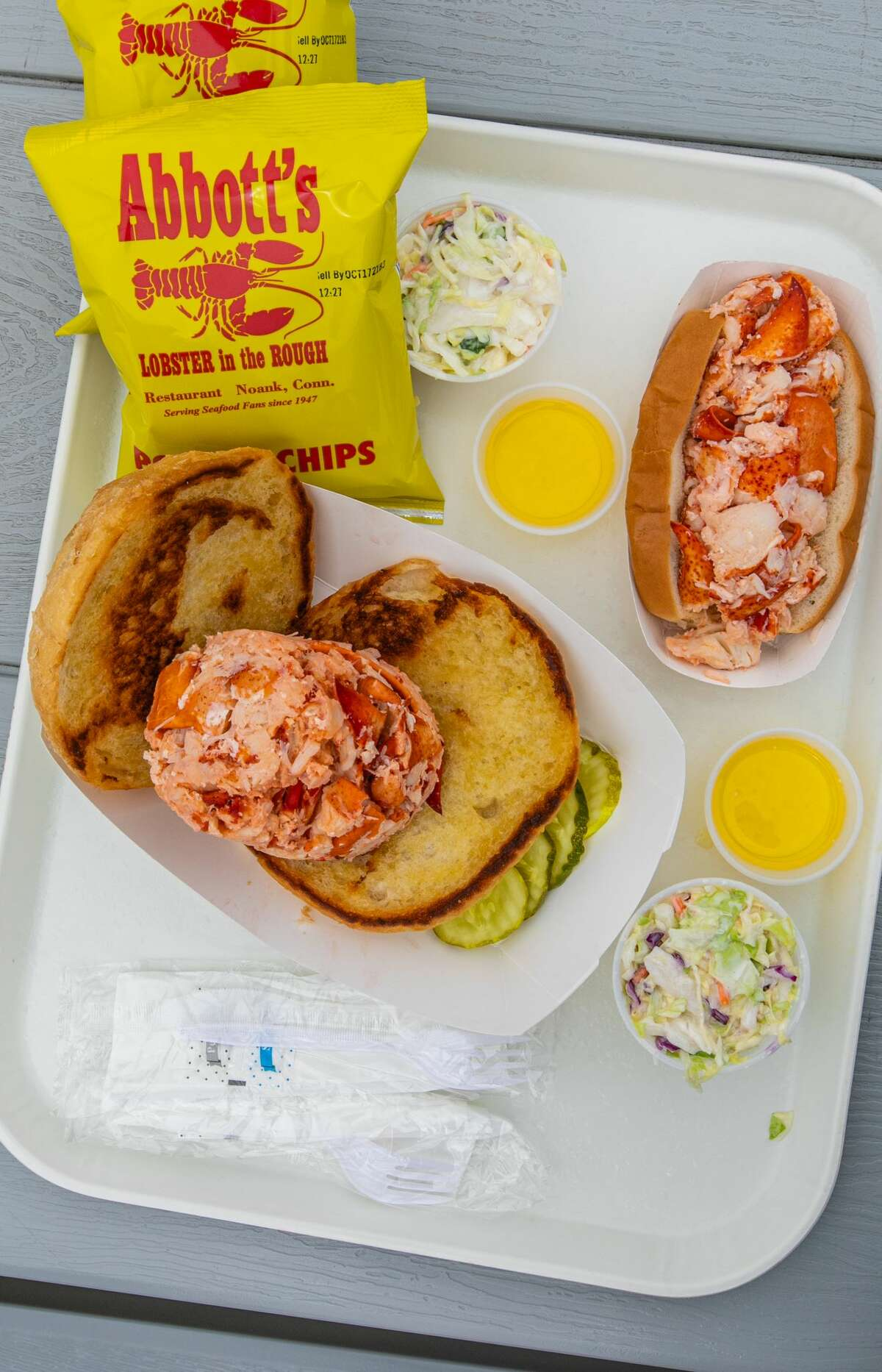 """An """"OMG Hot Lobster Roll"""" (front) and an """"LOL Hot Lobster Roll"""" at Abbott's in Noank, Conn. on June, 2021."""