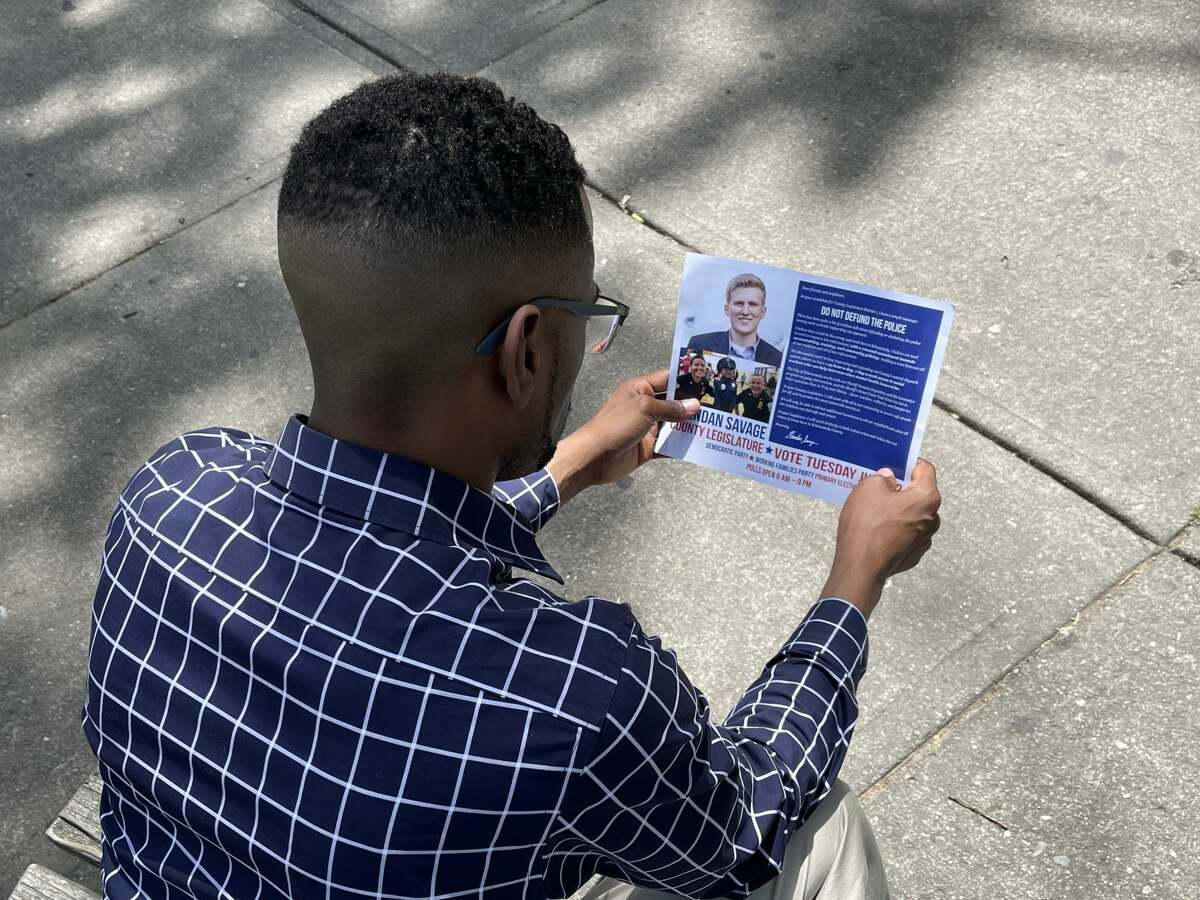 Omar McGill, a candidate for Schenectady County Legislature, studies a campaign mailer on Saturday, June 12, 2021, issued by his opponent, Brendan Savage, that his supporters contend unfairly insinuates McGill is in favor of defunding the police.