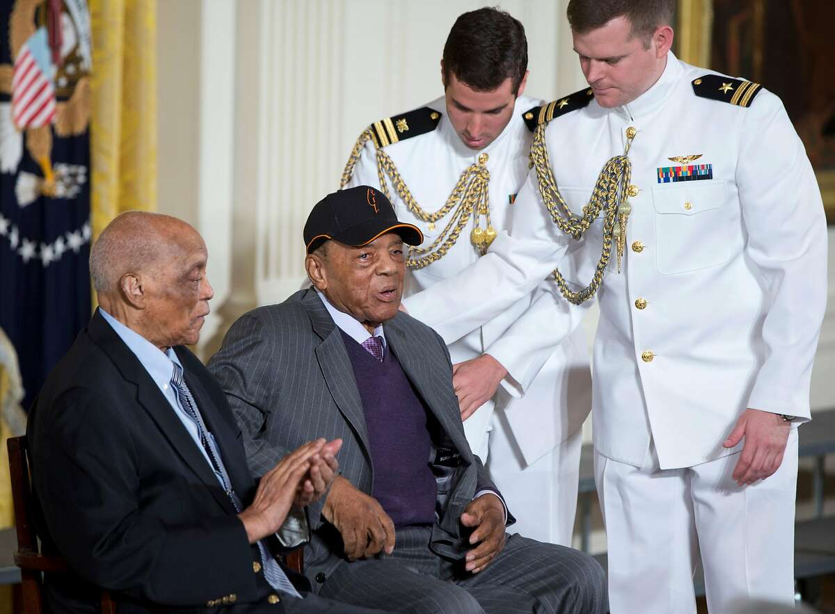 Hall of Fame baseball player Monte Irvin, left, and Willie Mays, are helped to their seats on stage in the East Room of the White House in Washington, Thursday, June 4, 2015, prior to a ceremony where President Barack Obama honored the 2104 World Series baseball champions. (AP Photo/Carolyn Kaster)