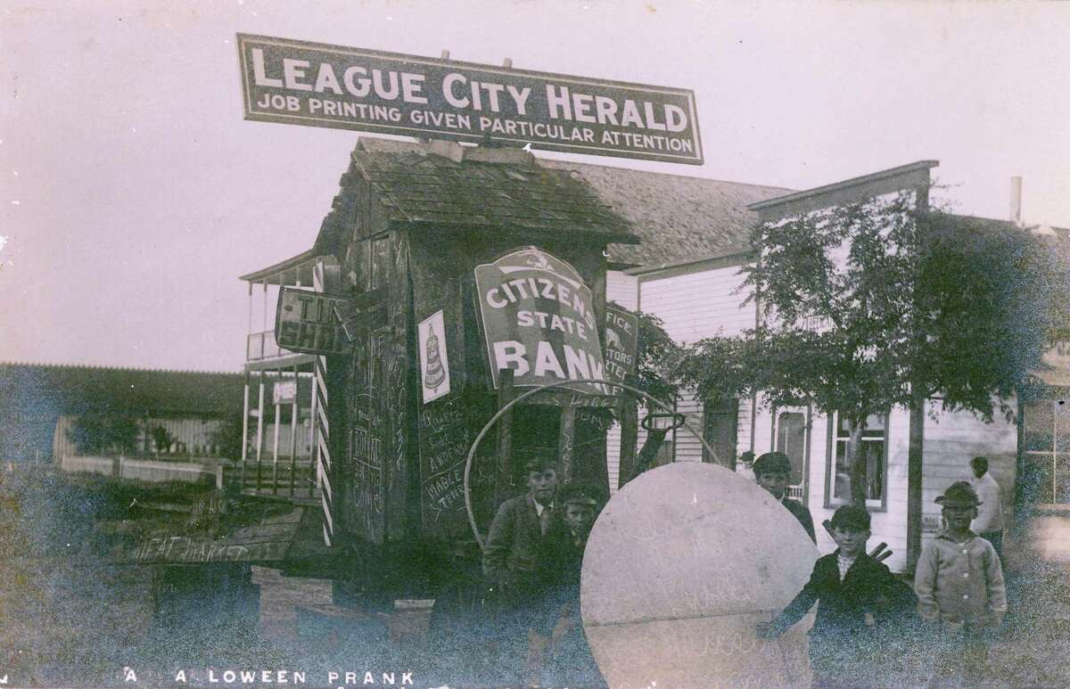 A postcard photo shows a Halloween prank in which local business signs were relocated to a spot on Main Street.