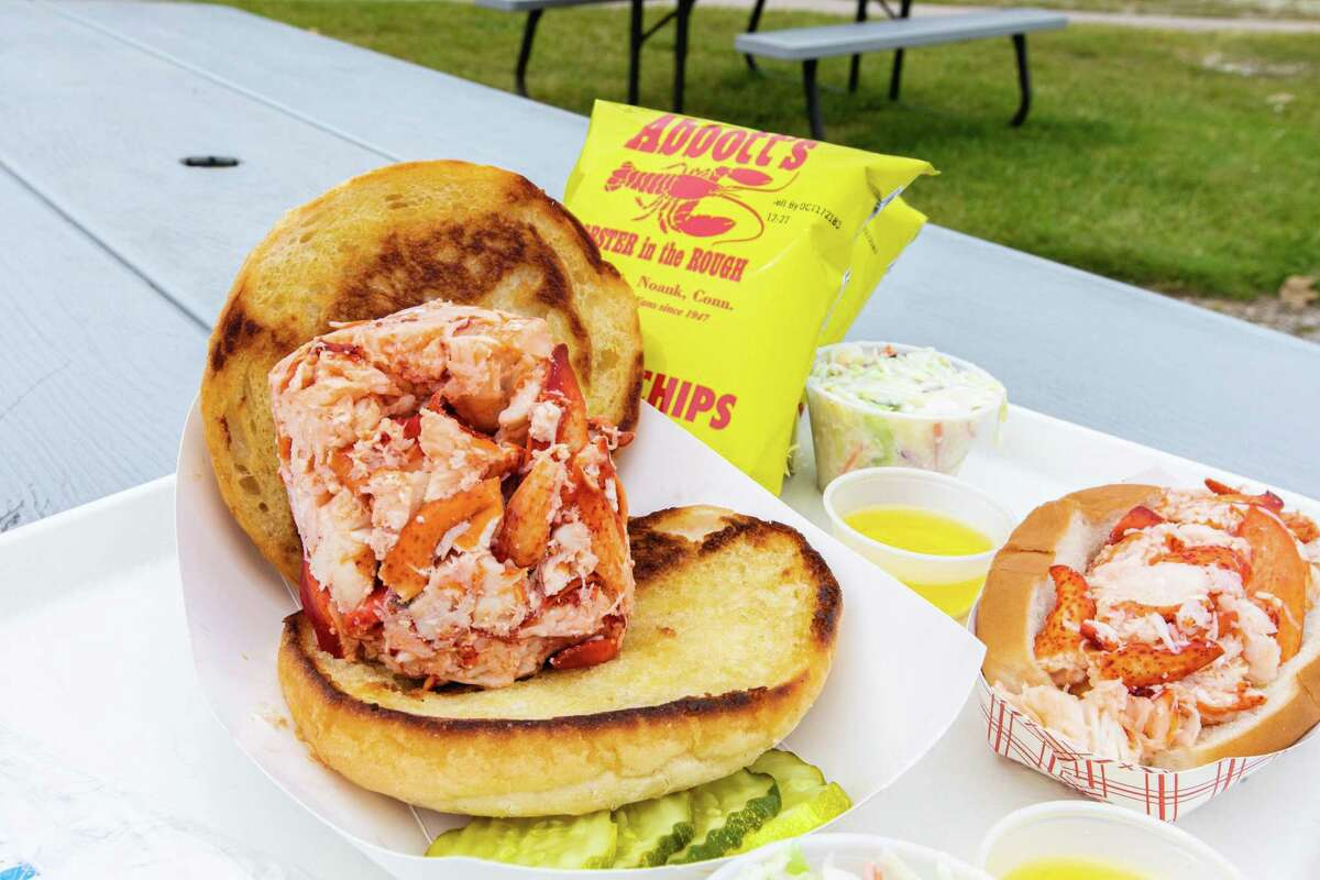 """An """"OMG Hot Lobster Roll"""" (front) and an """"LOL Hot Lobster Roll"""" at Abbott's Lobster in the Rough in Noank."""