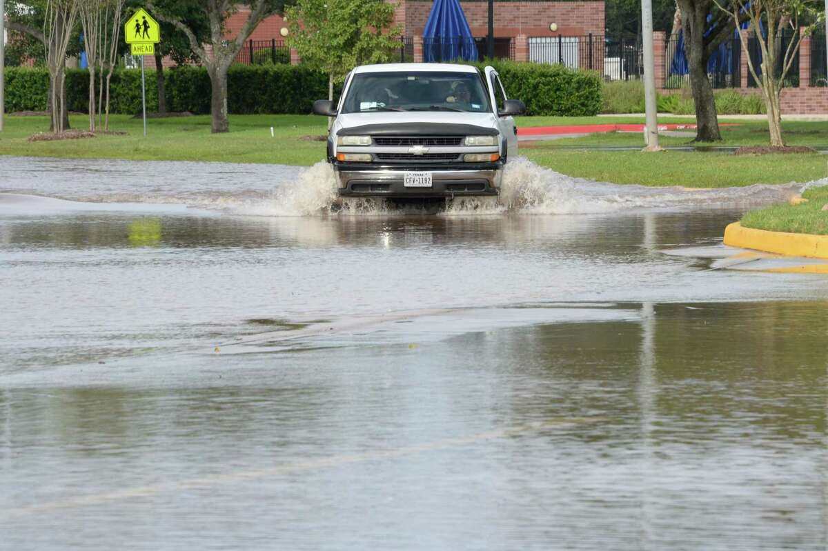 A pickup truck negotiates flooded residential streets in the Lakes of Austin Parkway in Sugar Land on Aug. 30, 2017.