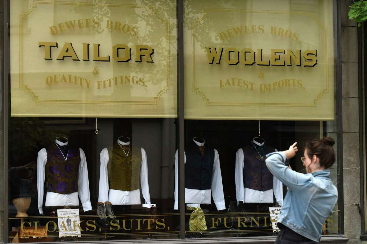 A passerby take a picture of the Monument Square storefront decorated for the HBO series 'The Gilded Age' on Monday, June 14, 2021, as crews head into the final days of downtown production in Troy, N.Y. (Will Waldron/Times Union)