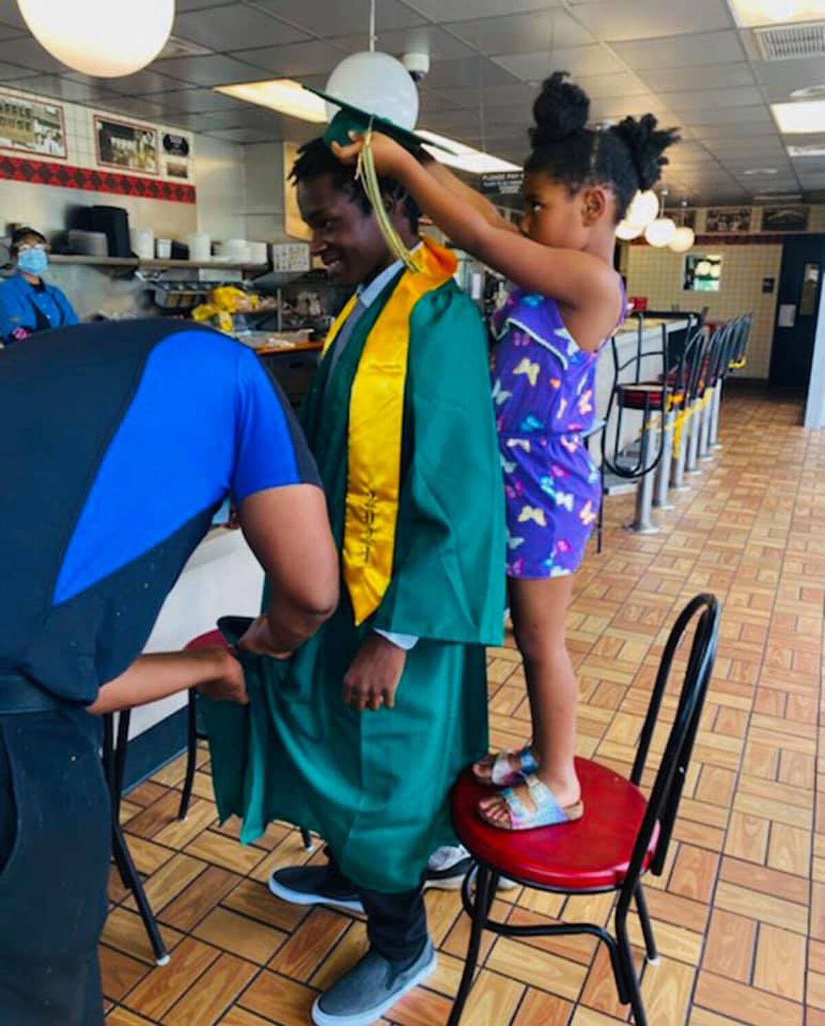 Daleena, 5, a Waffle House employee's daughter, places a graduation cap on Harrison.