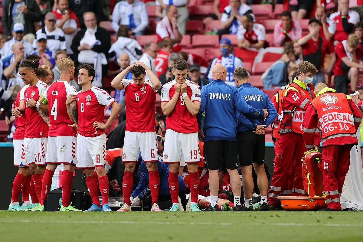 Players and staff react as paramedics attend to Denmark midfielder Christian Eriksen after he collapsed on the pitch during a UEFA EURO 2020 Group B football match against Finland at the Parken Stadium in Copenhagen, Denmark, on Saturday, June 12, 2021. (Friedemann Vogel/POOL/AFP/Getty Images/TNS)
