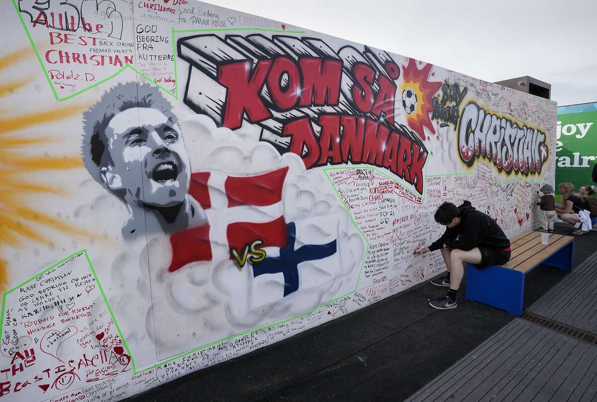 People writing well wishes at a graffiti for Danish player Christian Eriksen on a wall at the fanzone in Copenhagen, Denmark, Monday, June 14, 2021. Eriksen remains in hospital after he collapsed on the pitch during the European Championship game against Finland on Saturday and needed CPR from medical staff before regaining consciousness. (AP Photo/Martin Meissner)