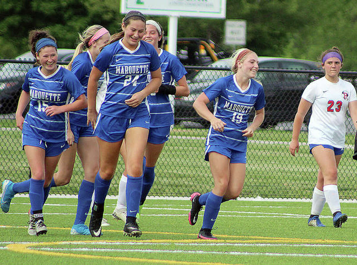 Marquette players Madelyn Smith (15), Anna Rodgers (24) and Emma Anselm (19) celebrate a goal this season against Roxana.