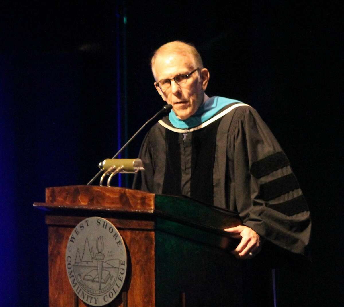 West Shore Community College executive director of college relations Thom Hawley speaks during a commencement ceremony at the Center Stage Theater on April 29. Hawley recently retired after over 19 years with the college.