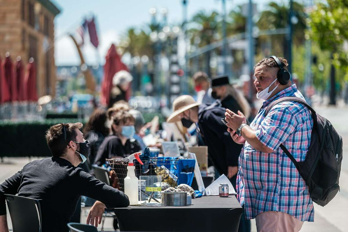 David (no last name given) speaks with Ethan Thompson with Hog Island Oyster Co. during a job fair for Ferry Building businesses in San Francisco on Monday, June 14, 2021.