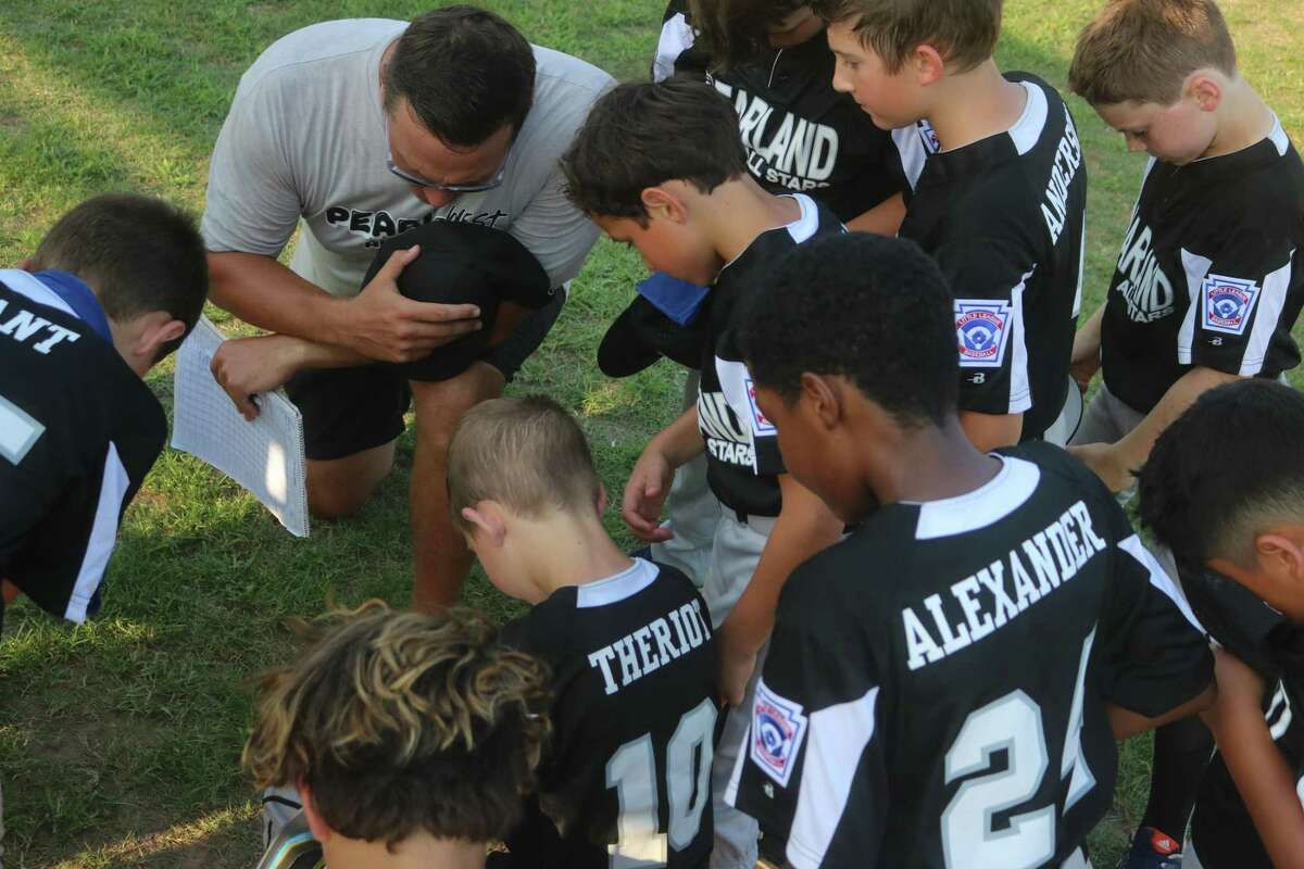Pearland West manager Layne Wyatt holds a pregame prayer with his boys, prior to a Saturday game at John Paul Field. Wyatt is a former high school athlete.