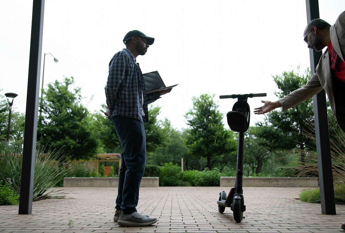 University of Texas at San Antonio doctoral student and research assistant Raveen Wijewickrama, left, and assistant professor Dr. Murtuza Jadliwala show how a scooter is being used as a means to collect data to advance Artificial Intelligence technology at UTSA on June 9, 2021.