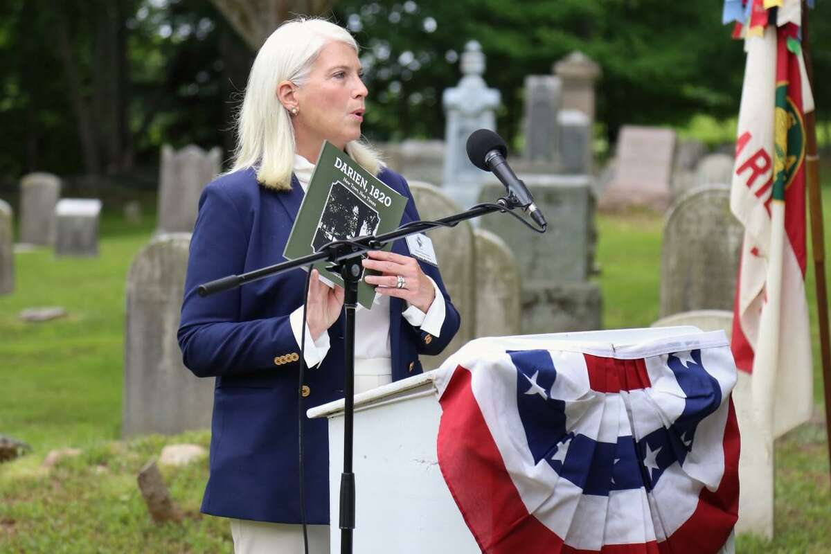 """First Selectman Jayme Stevenson shares from the book """"Darien 1820: New Town, New Times,"""" by Kenneth Reiss, historian with the Museum of Darien, at the Bicentennial Day ceremony at Slawson Cemetery on Saturday."""