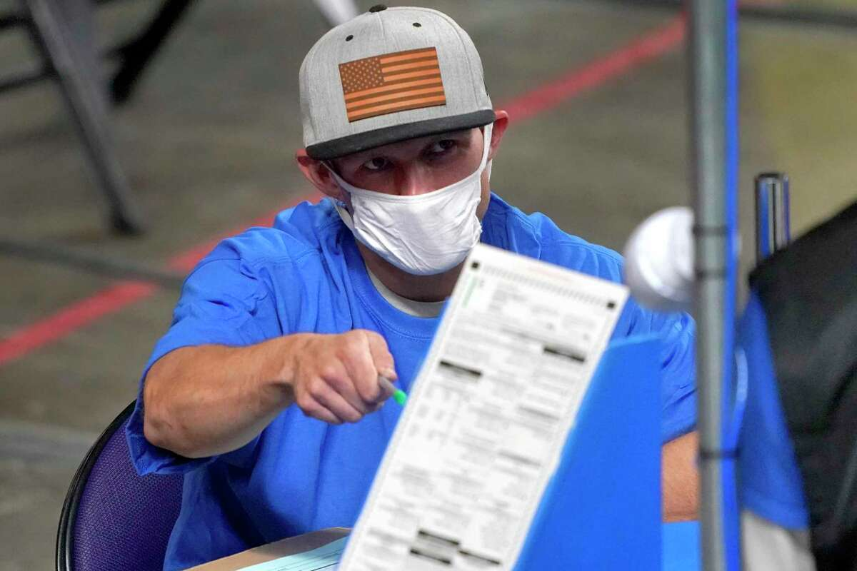 In this May 6, 2021 photo, Maricopa County ballots cast in the 2020 general election are examined and recounted by contractors working for Florida-based company, Cyber Ninjas at Veterans Memorial Coliseum in Phoenix.