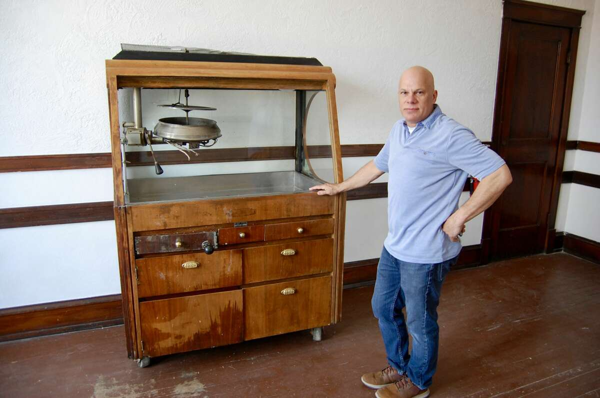 Shawn Sims, president of the Miners' Institute Foundation, stands with an authentic 1945 popcorn machine. The company has verified making the machine via its serial number Sims has. The two are working out a way to obtain original parts and get it up and running.