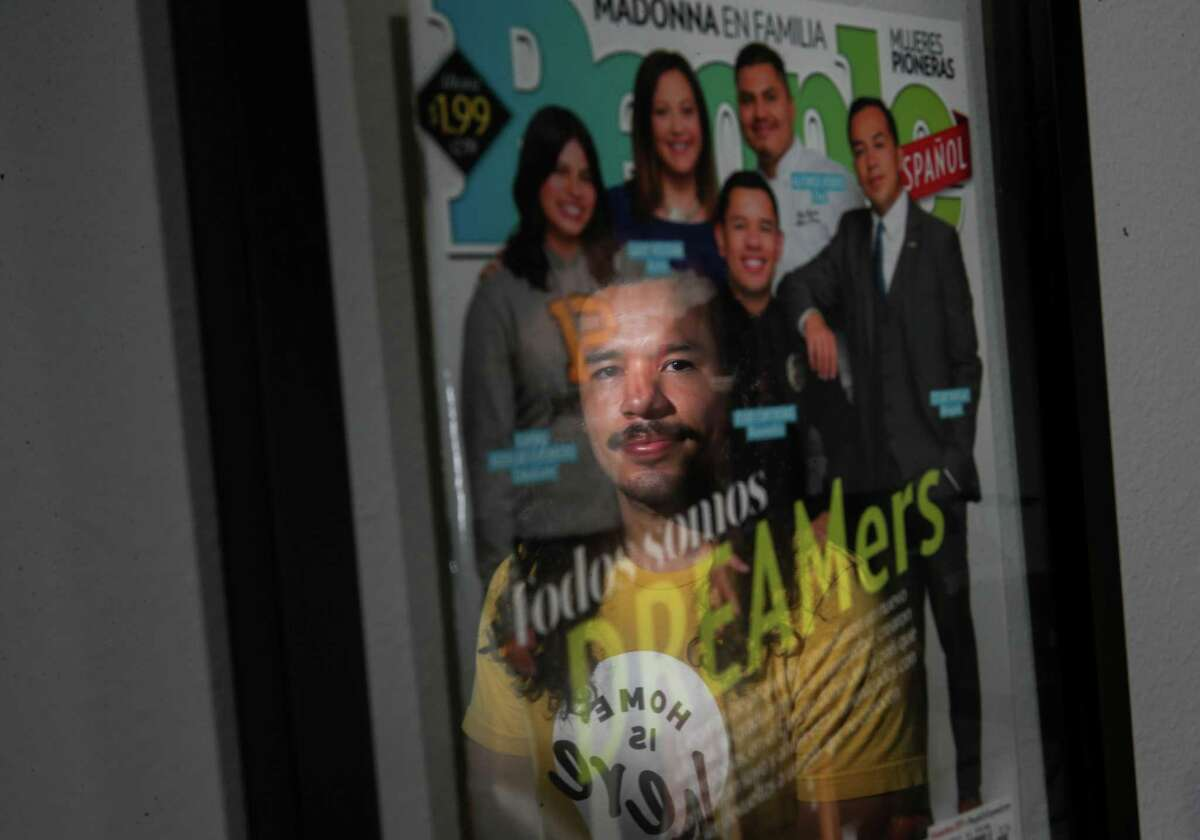 """Jesus Contreras, a Houston-area paramedic, poses for a portrait while reflected in a cover of People en Español magazine Sunday, June 13, 2021, at his apartment in Houston. Contreras was pictured on the cover of the November 2017 issue. """"We're just scratching the surface with this one person here,"""" he said of himself. """"It's just the surface of what the whole immigrant community is."""""""