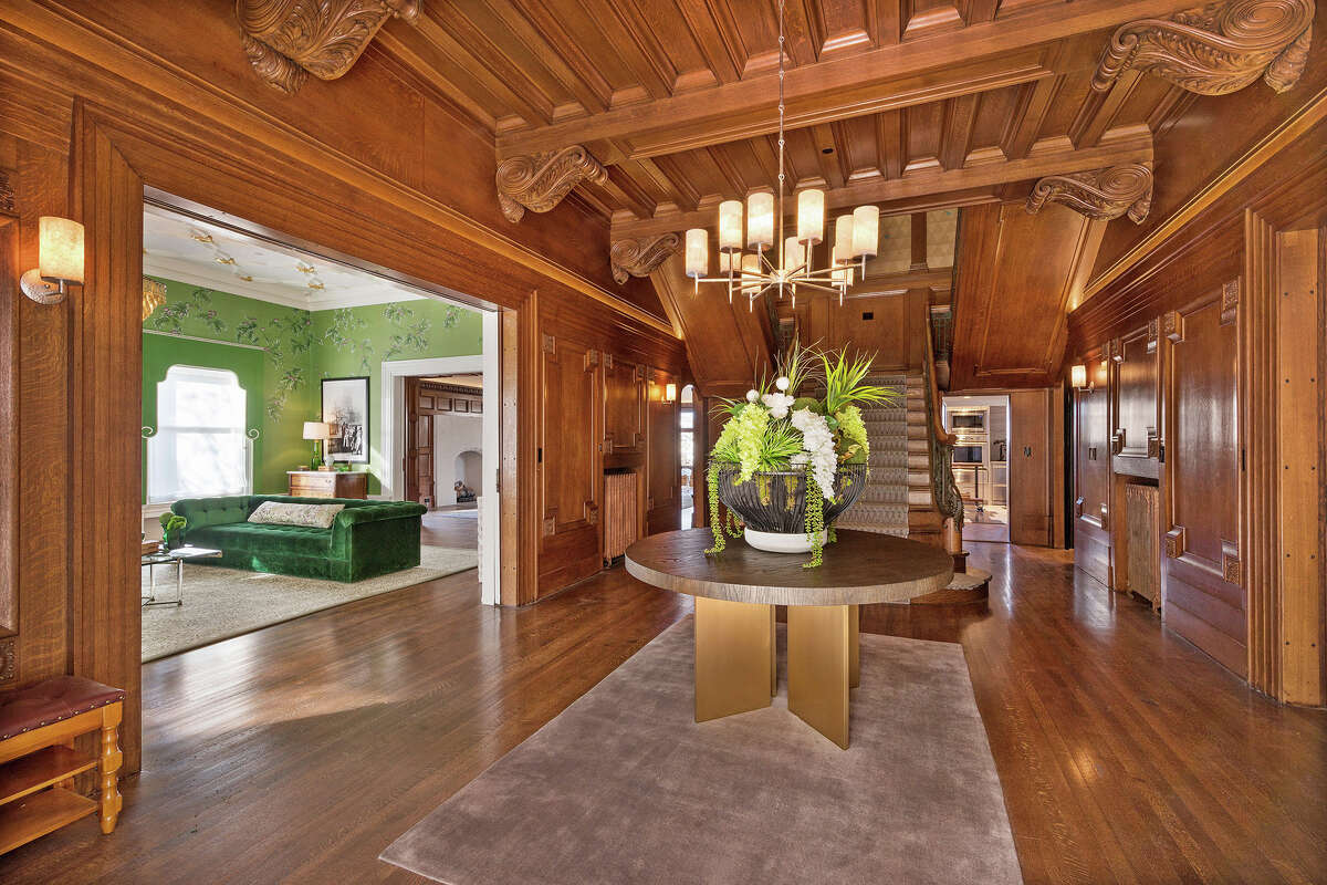 The dramatic foyer is paneled completely in dark, gleaming wood.