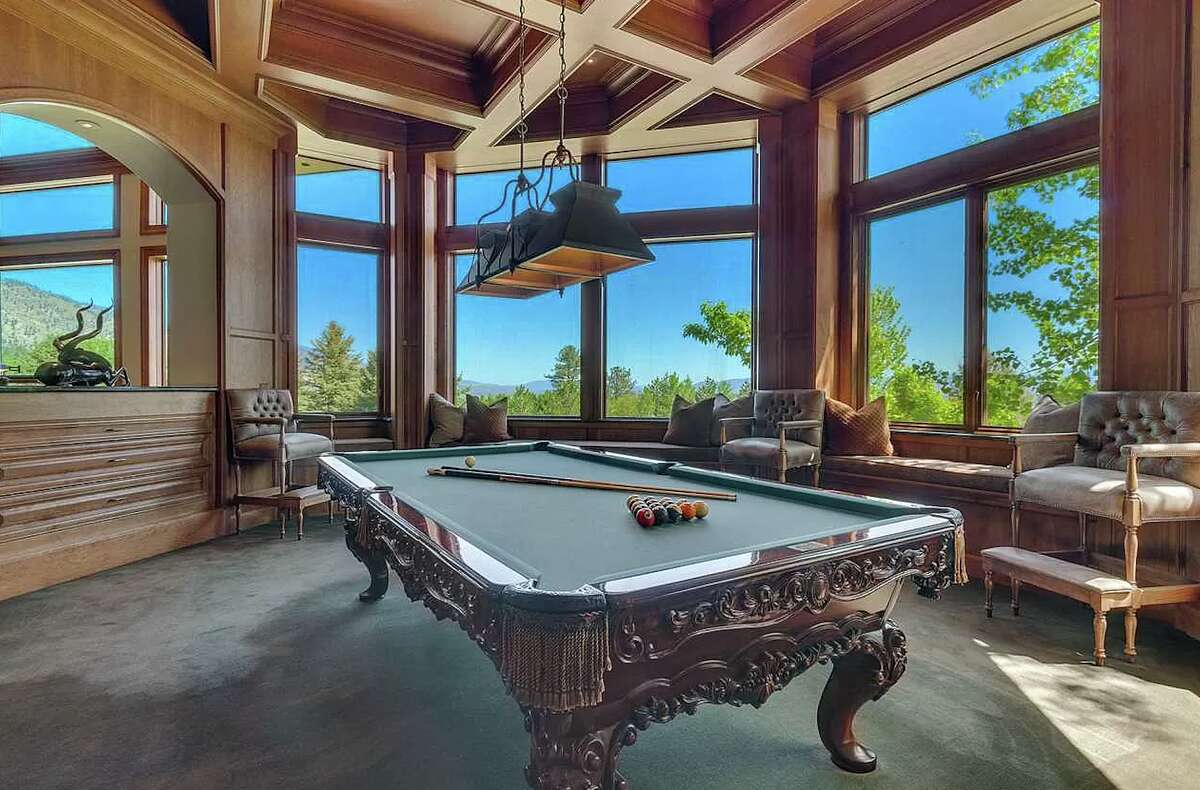 More spectator seating can be found in the billiards room, which has a custom coffered ceiling and built-in green marble bar.