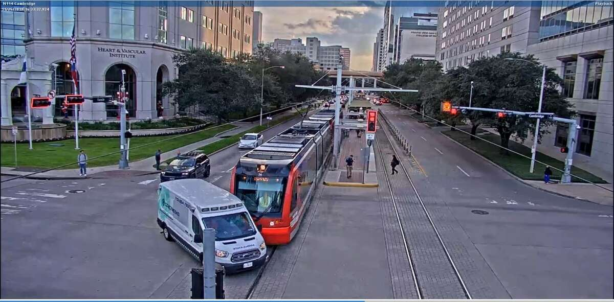 A screenshot from a traffic recording shows a collision between an EMS vehicle and a Metrorail Houston train on Fannin Street and Cambridge Street.