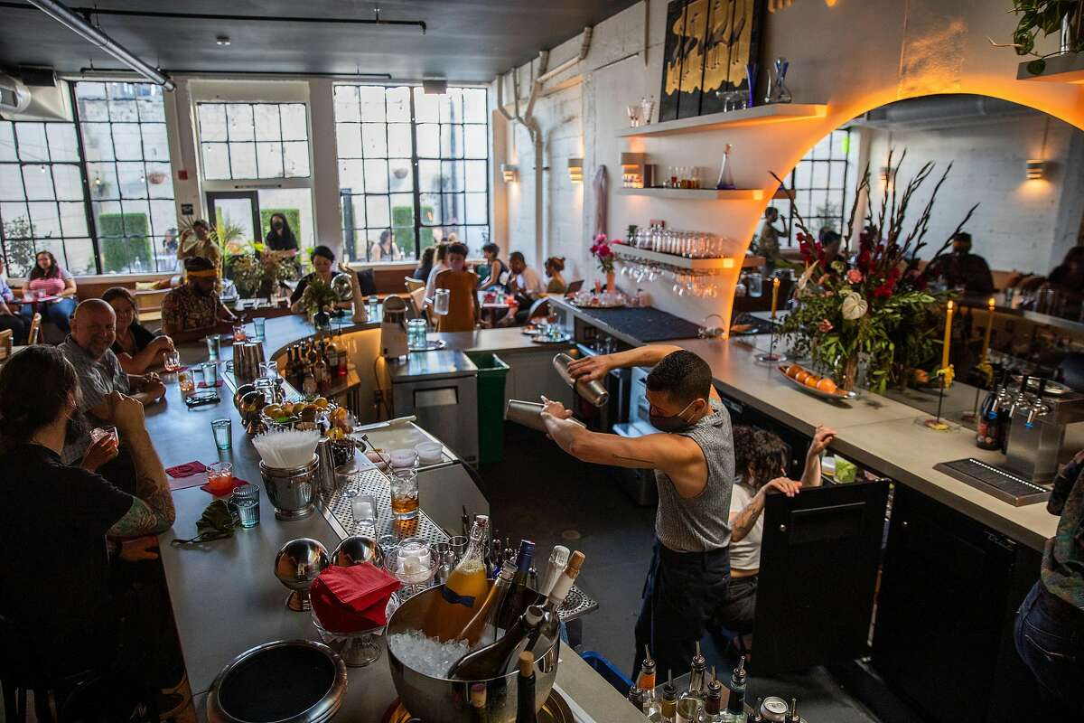 Julian Arreola (center) makes drinks for customers at Friends & Family in Oakland.