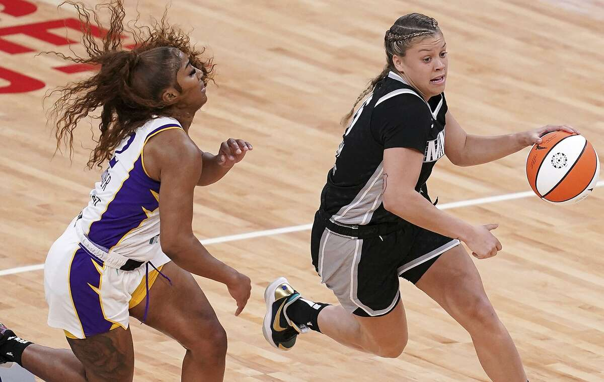 Minnesota Lynx guard Rachel Banham (15) dries past Los Angeles Sparks guard Te'a Cooper (2) during the first quarter of a WNBA basketball game Saturday, June 12, 2021, in Minneapolis. (Anthony Souffle/Star Tribune via AP)