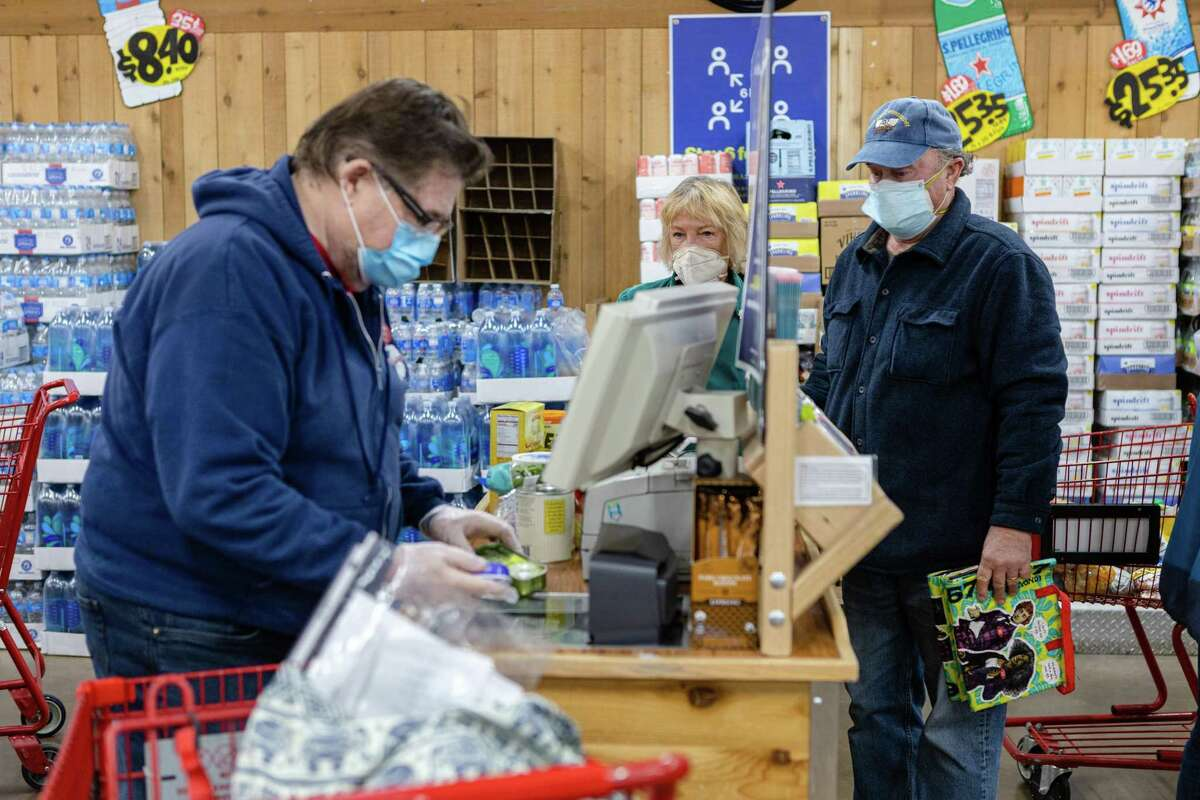 Richard Steil, cashier at Trader Joe's, scans groceries for customer Wes and Doris Watkins in San Francisco.
