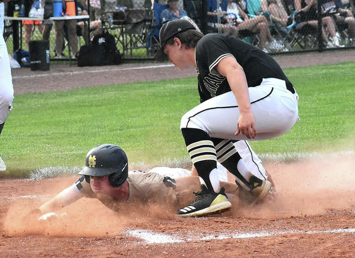 Father McGivney's Drew Sowerwine slides under the tag at home plate for the first run of the game.