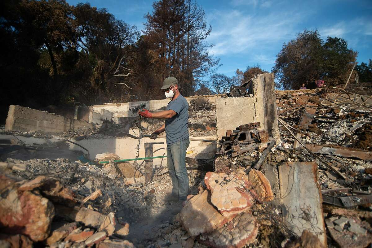 Chris Jones sifts through the remains of Jon and Elizabeth Payne's house in Boulder Creek on Nov. 1, 2020. Payne is an accomplished musician who had just finished work on a home studio when the CZU Lightning Complex Fire swept through and destroyed his house. Jones has known Payne since they were 12 and was renting from him at the time of the fire. The Paynes plan on rebuilding their residence, which was an unofficial musician's retreat of sorts.