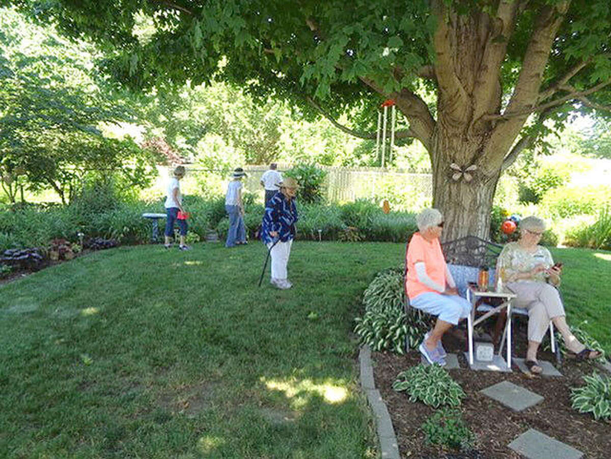 Some of those taking part in Sunday's garden walk sponsored by Hope Circle of Centenary United Methodist Church take a break in the shade.