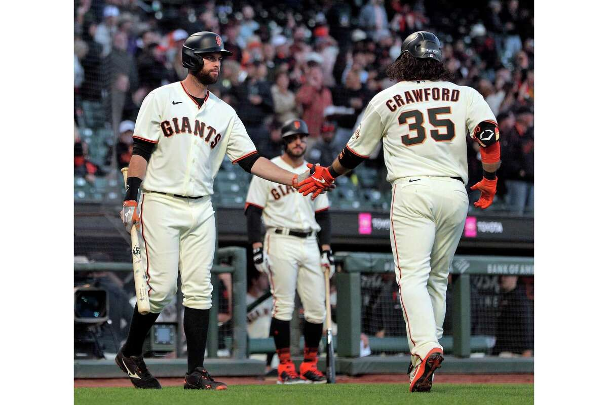 Brandon Belt (9) high fives Brandon Crawford (35) after he rounded the bases following his two-run homerun in the fifth inning as the San Francisco Giants played the Arizona Diamondbacks at Oracle Park in San Francisco, Calif., on Monday, June 14, 2021.