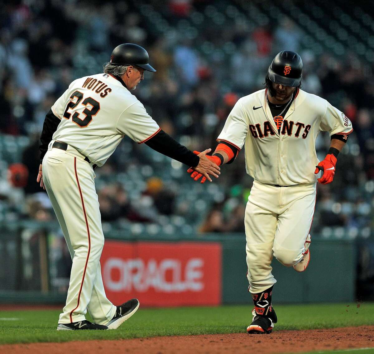 Brandon Crawford (35) high fives third base coach Ron Wotus (23) after hitting his two-run homerun in the fifth inning as the San Francisco Giants played the Arizona Diamondbacks at Oracle Park in San Francisco, Calif., on Monday, June 14, 2021.