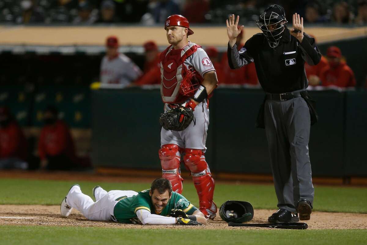 OAKLAND, CALIFORNIA - JUNE 14: Chad Pinder #4 of the Oakland Athletics lies on the ground after being hit by a pitch from Junior Guerra of the Los Angeles Angels in the bottom of the seventh inning at RingCentral Coliseum on June 14, 2021 in Oakland, California. (Photo by Lachlan Cunningham/Getty Images)