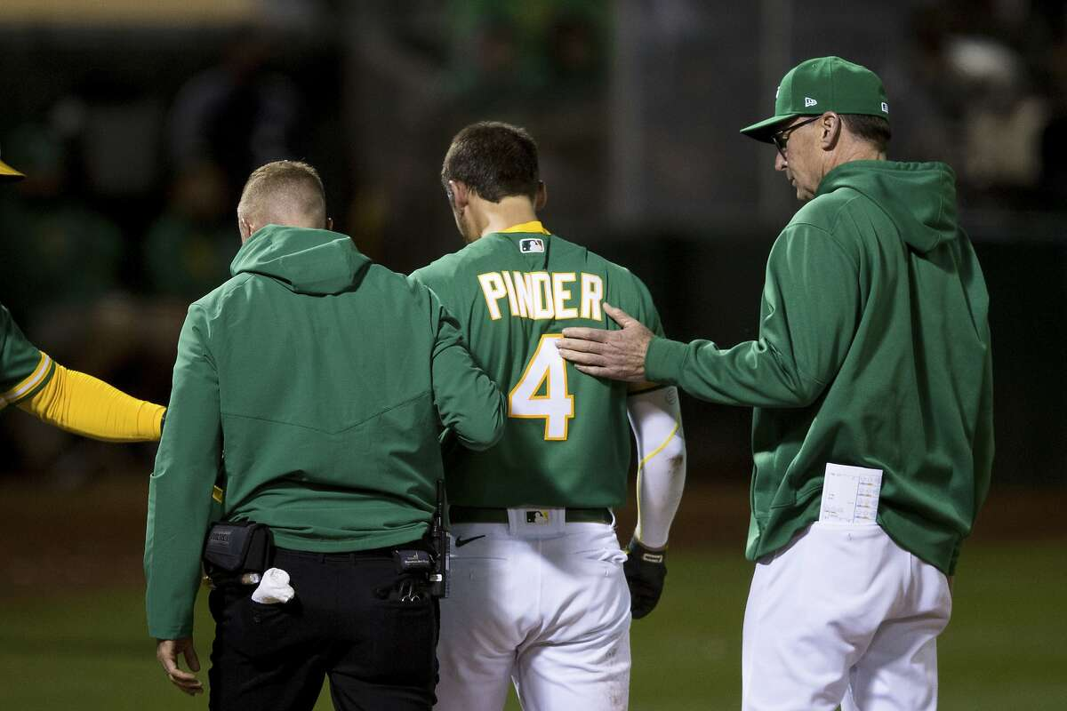 Oakland Athletics manager Bob Melvin, right, and head trainer Nick Paparesta, left, tend Chad Pinder (4) after he was hit by a wild pitch by Los Angeles Angels relief pitcher Junior Guerra (not seen) during the seventh inning of a baseball game in Oakland, Calif., Monday, June 14, 2021. (AP Photo/John Hefti)
