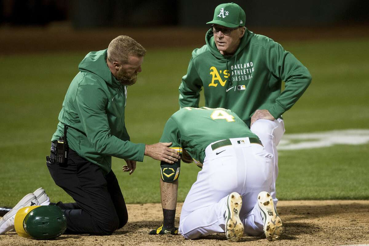 Oakland Athletics manager Bob Melvin, right, and head trainer Nick Paparesta, left, tend to Chad Pinder (4) after he was hit by a wild pitch by Los Angeles Angels relief pitcher Junior Guerra during the seventh inning of a baseball game in Oakland, Calif., Monday, June 14, 2021. (AP Photo/John Hefti)