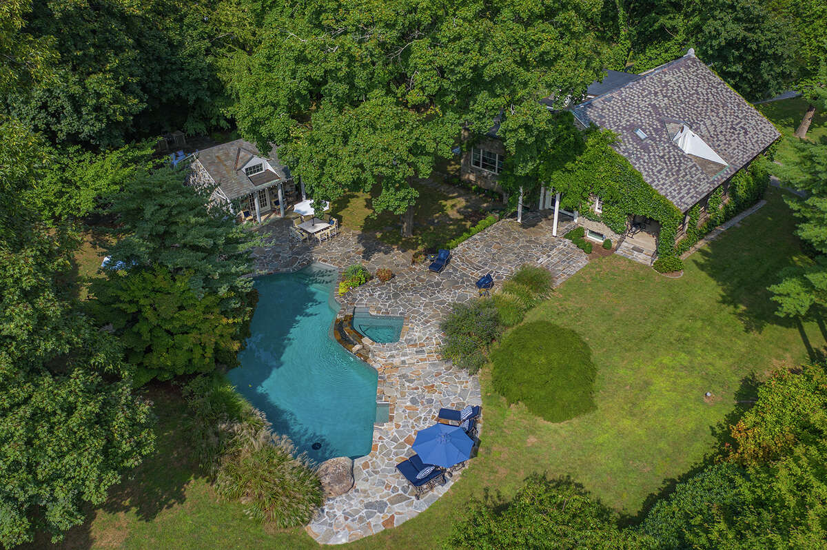 TheFraser Lane homesits on just over 2 acres of land and features a heated Gunite pool, cabana and hot tub on the property.