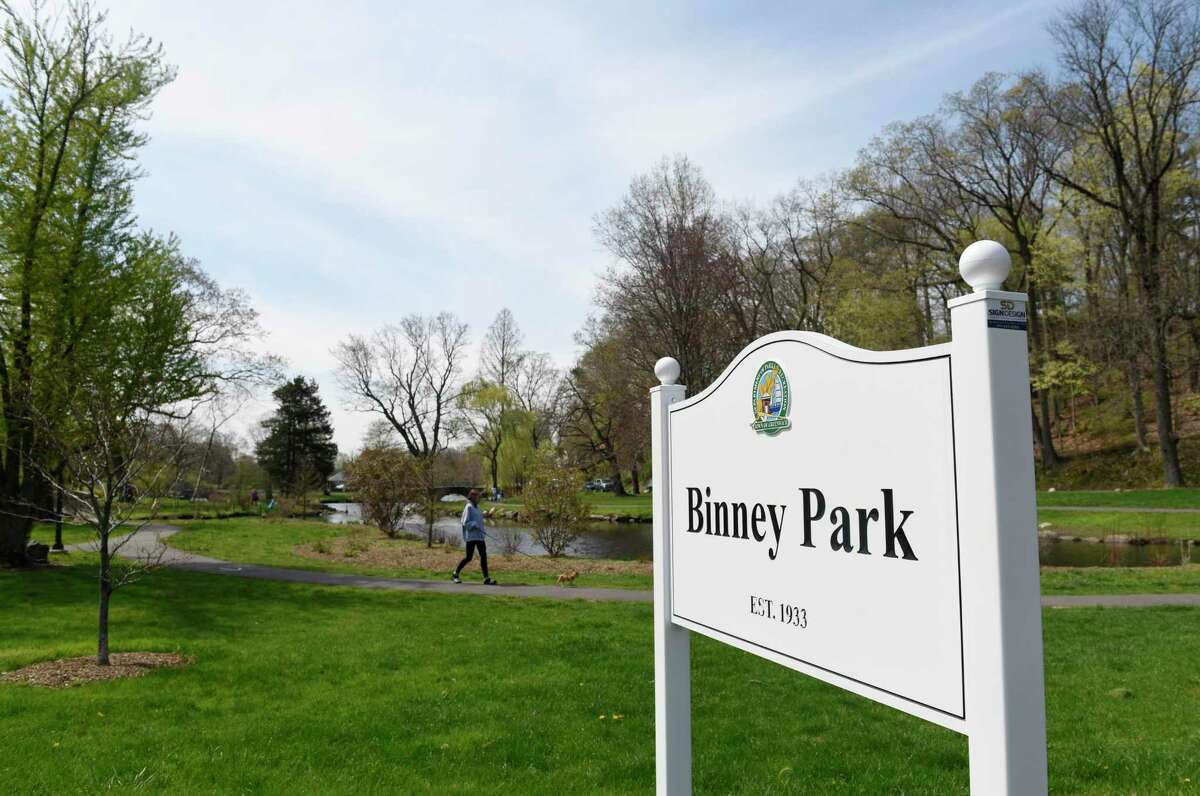 A woman walks her dog at Binney Park in Old Greenwich, Conn. Tuesday, April 20, 2021. The park is slated to host a festival and boutique on Saturday, but there have been questions about what it is raising money for and if it is a proper use of the park.