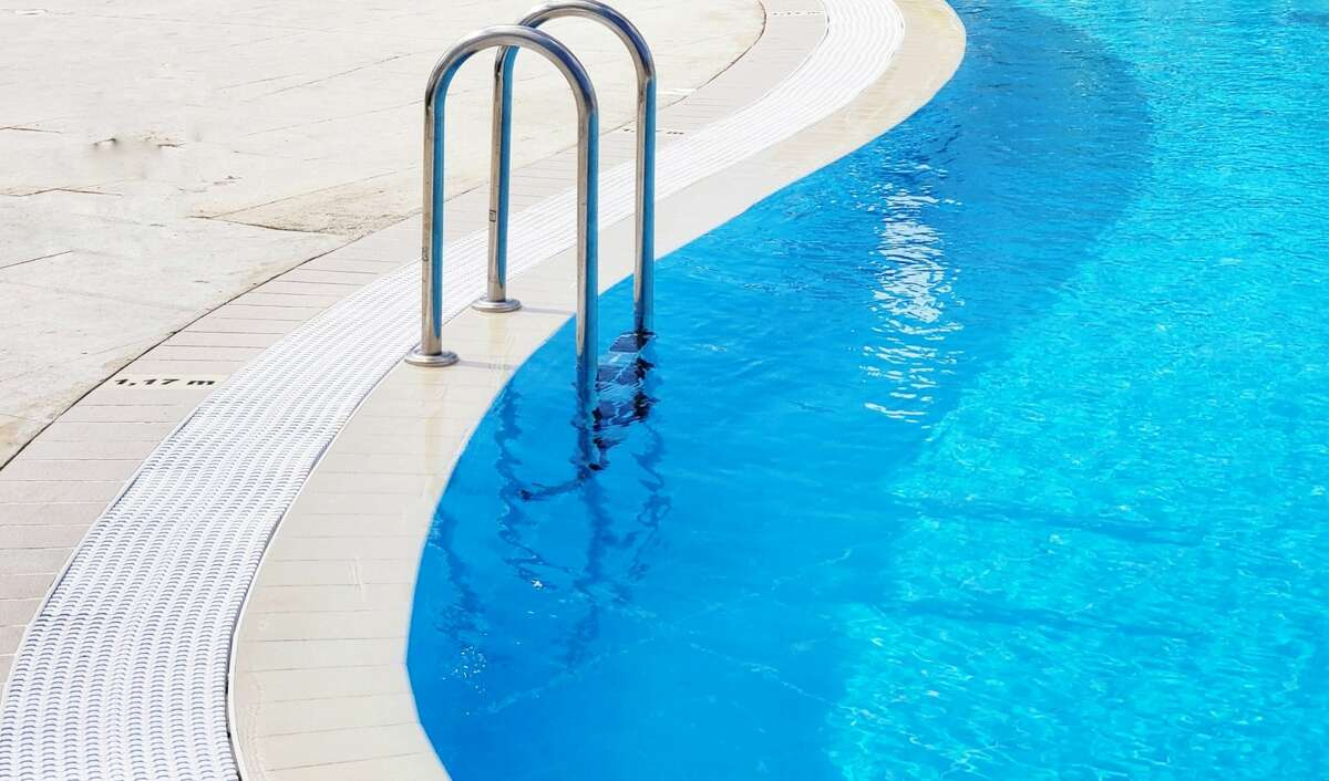 A minimalist view of curves in a swimming pool featuring the arched hand rails and ladder.