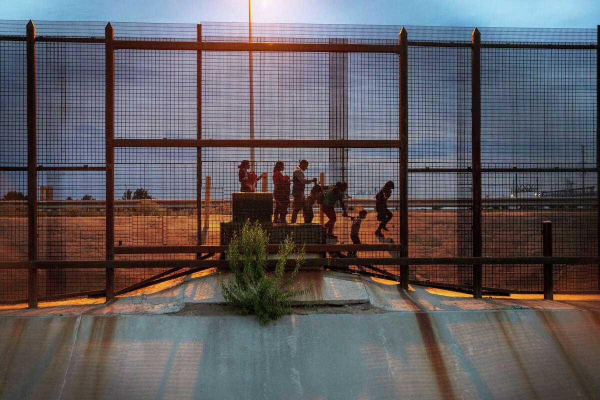FILE -- A group of migrants from Guatemala walk along the Mexican side of the border wall looking for an opportunity to enter the United States to seek asylum, near El Paso, Texas, June 28, 2019. The Supreme Court on Friday, July 26, 2019, allowed the Trump administration to move forward with plans to build a wall along parts of America's southern border while litigation over paying for it proceeds. (Ilana Panich-Linsman/The New York Times)