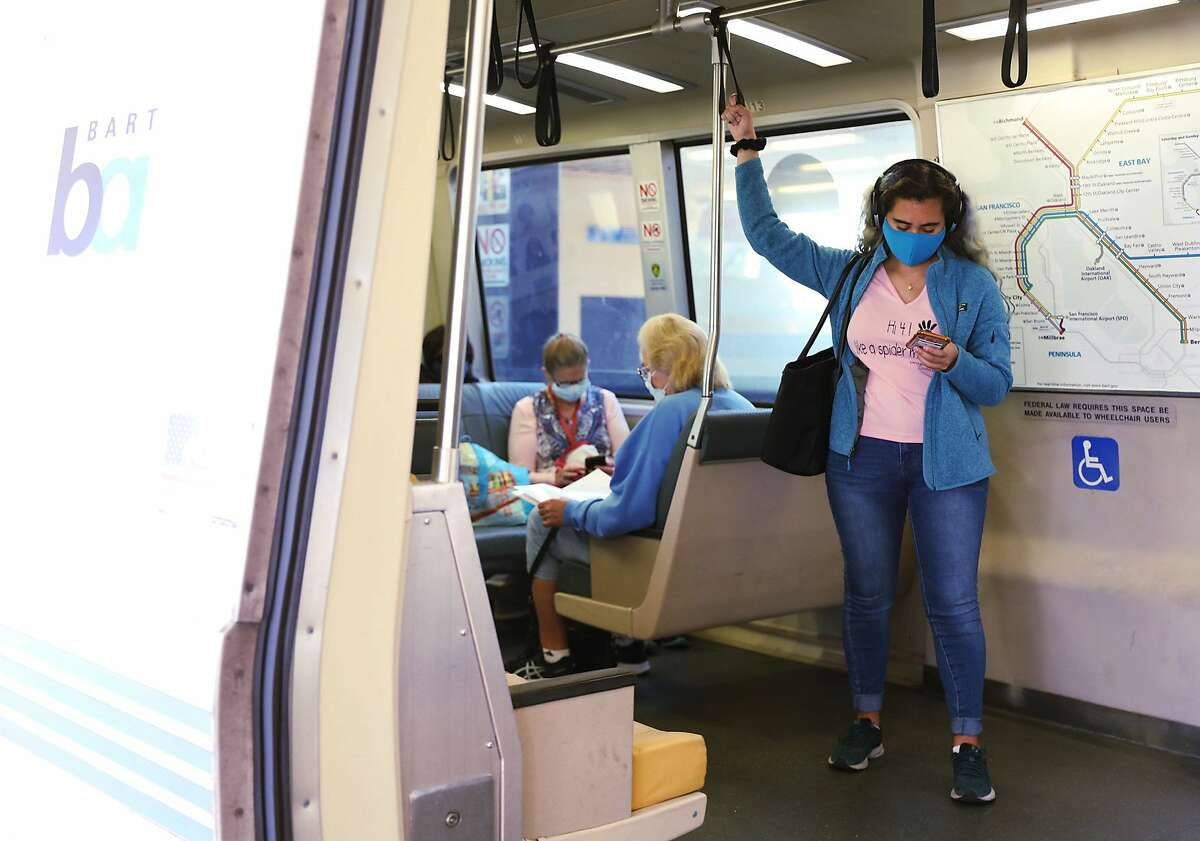 Morning commuters wear masks on a San Francisco bound train at MacArthur Station in Oakland. California lifted nearly all of its pandemic restrictions and masks on public transit were one of the exceptions.