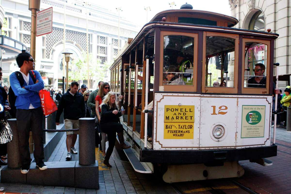 Visitors and tourists board the historic San Francisco cable cars at the Market and Powell Street cable car stop in San Francisco. The landmark service will return in September after being suspended during the pandemic.