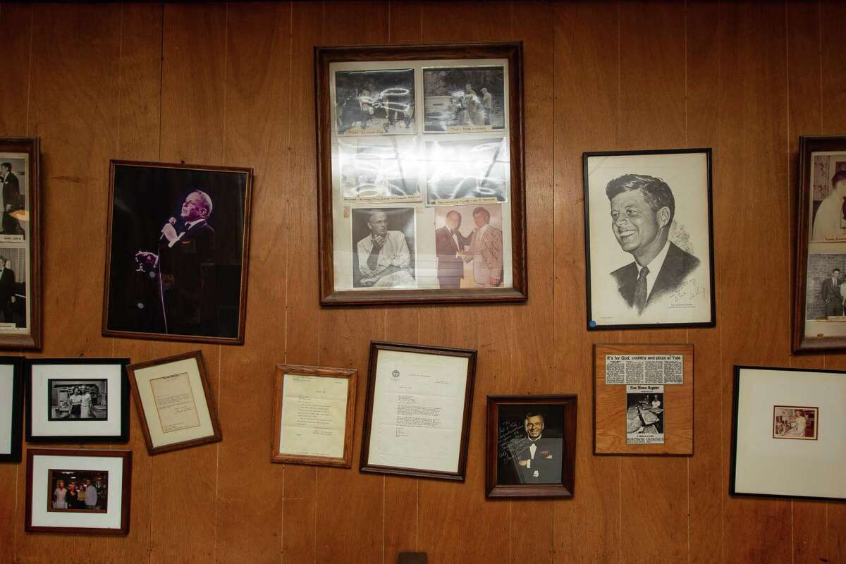 Photos and articles hang on the walls of Sally's Apizza in New Haven.