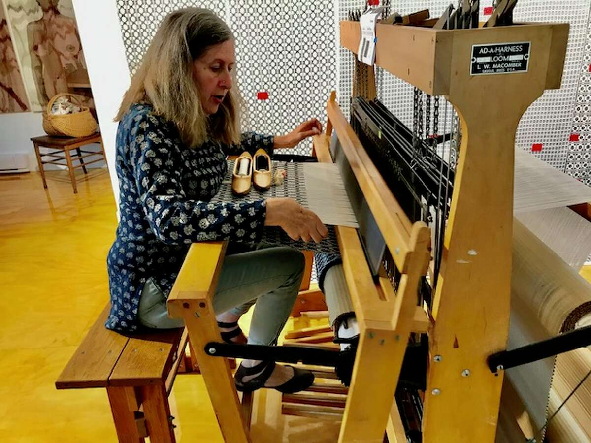 Weaver Cyndy Barbone at her handloom, where she is at work on a monumental project to commemorate 48,475 coronavirus victims who died in New York in one year with woven roses. (Paul Grondahl / Times Union)
