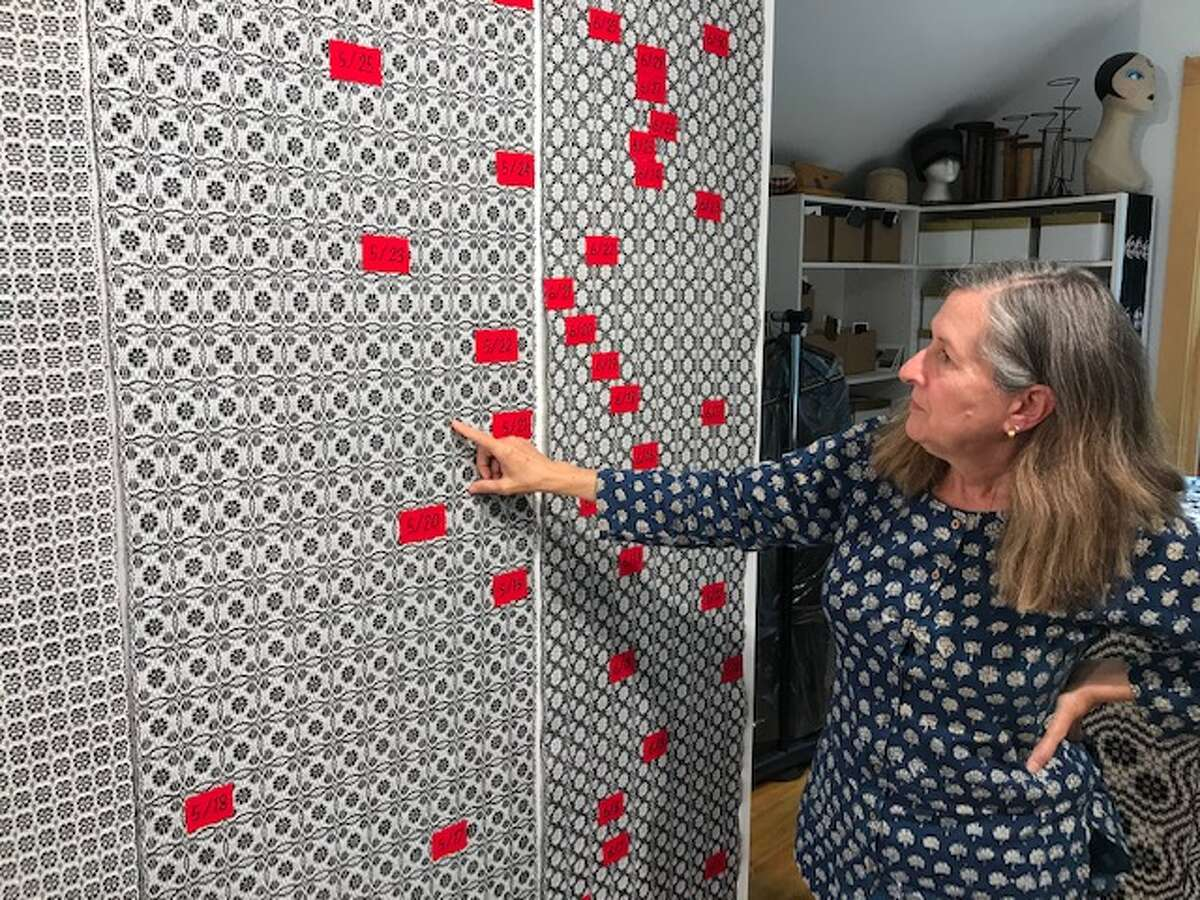 """Cyndy Barbone's """"A Rose is a Rose is a Rose"""" project includes red embroidered days for the daily COVID-19 death toll in New York. (Paul Grondahl / Times Union)"""
