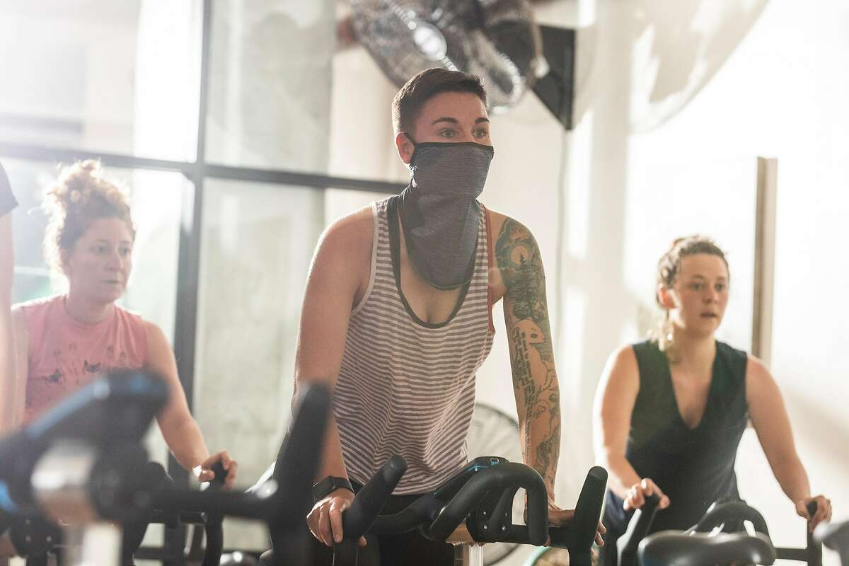 Tanya Wischerath wears a face covering at a cycle class at 17th Street Athletic Club in San Francisco on the day California reopens its economy. Mask wearing was optional for patrons of the studio.