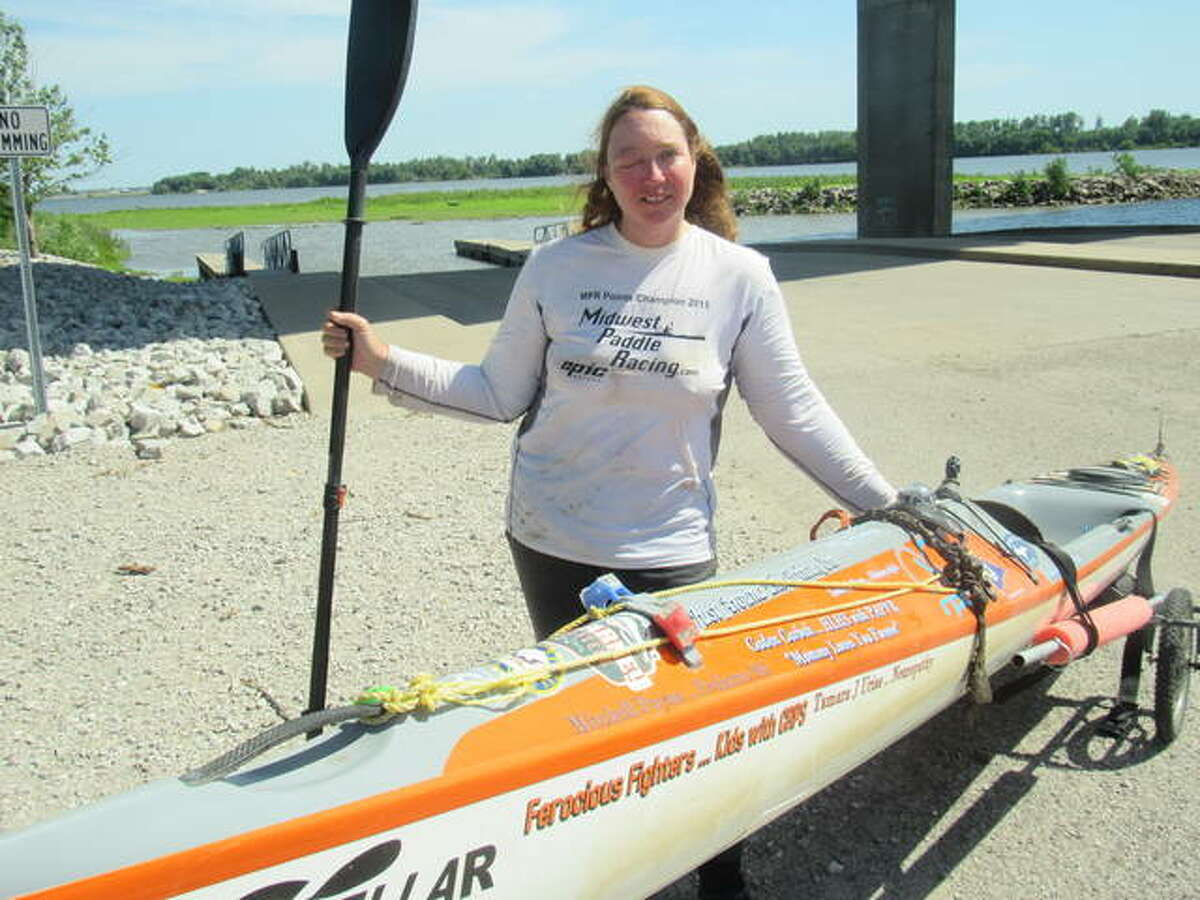 Competitive kayaker Traci Lynn Martin, of Kansas City, Missouri, stands beside her kayak Monday in Alton. Martin is on a quest to set a world record for the fastest time a solo female kayaker to travel the Mississippi River.
