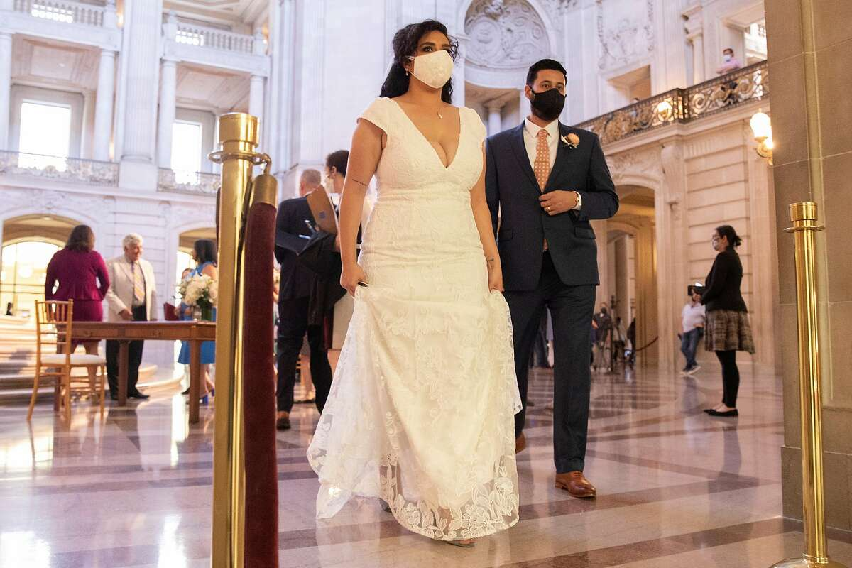 Eric Lara and Iyah Turminini wear masks after being married by Mayor London Breed during the very first indoor City Hall marriage ceremonies since the start of the pandemic following a Pride month kickoff celebration at San Francisco City Hall in San Francisco, Calif. Monday, June 7, 2021.