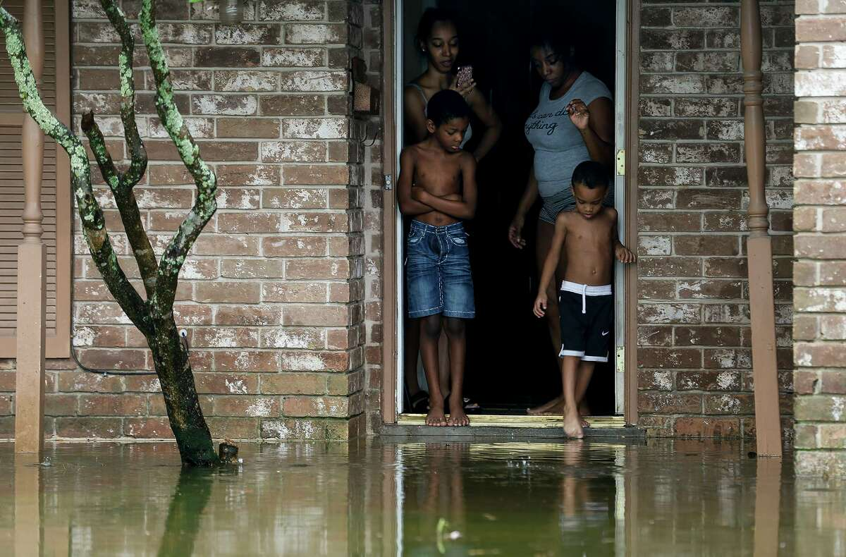 Cam'ron Maltie, 8, and Adrian Murray, 4, keep an eye on their flooded front lawn near Hobby Airport during Tropical Storm Beta on Sept. 22, 2020, in Houston. Their family has been living in the home for a year, and didn't know the neighborhood was prone to flooding.