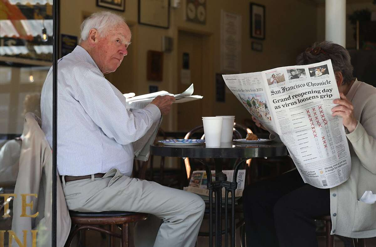 Jerry and Catherine Mutz enjoy their coffee and newspapers in Caffe Greco in San Francisco on the day California lifted nearly all of its pandemic restrictions.